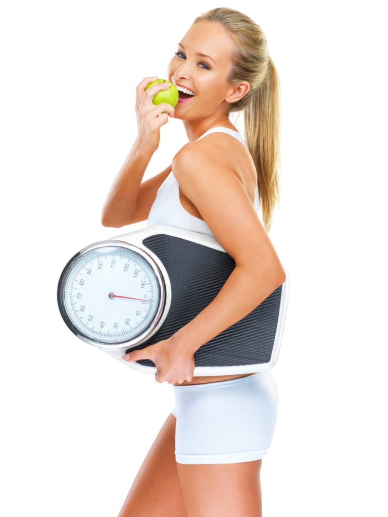 Shot of a young woman holding a scale and eating an apple - this is an alternative version of iStock file 47180376